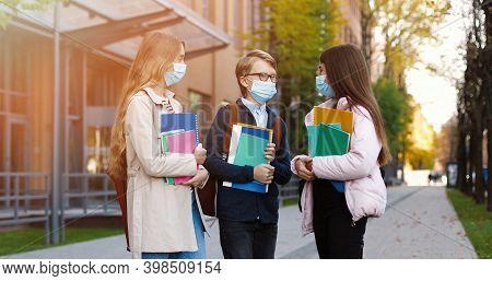Portrait Of Joyful Caucasian School Children Standing Outdoors And Talking After Classes. Happy Beau