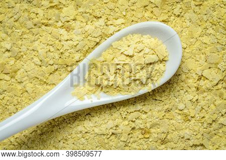 closeup of nutritional organic yeast flakes - background and texture with a white teaspoon, nutrition supplement, baking and cooking