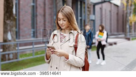 Portrait Of Caucasian Happy Beautiful Young School Girl Standing Outdoors And Texting On Smartphone.