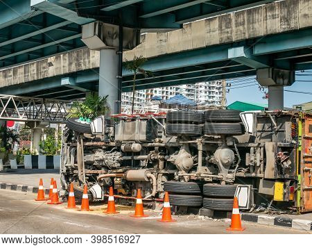 A View Of Under The Truck Carrying A Container Overturned On A Road Under A Bridge Over An Intersect