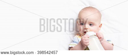 Baby Drinking Milk Frome Bottle. Banner With Copy Space. Cute Caucasian Infant In Striped Jumpsuit H