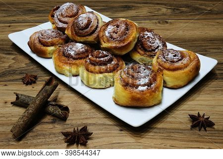 Cinnamon Rolls On White Plate Sprinkled With Icing Sugar With Decorations Of Badian Star And Cinnamo