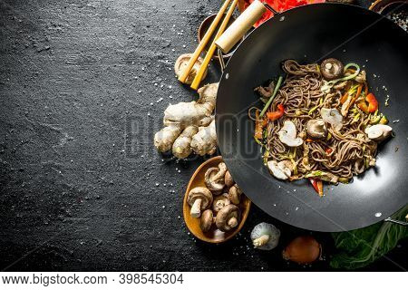 Prepared Chinese Noodles Wok Soba With Ignredients For Its Preparation. On Black Rustic Background