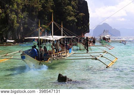 Palawan, Philippines - December 1, 2017: People Ride Outrigger Bangka Boat On Island Hopping Tour In