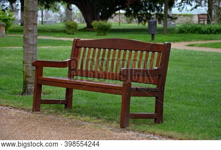park bench brown with backrest english type beige path thresh lawns wet rain rainy threshing