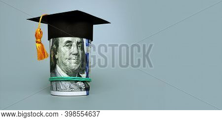 Loan Or Savings For College. Graduation Cap And Roll Of Cash.