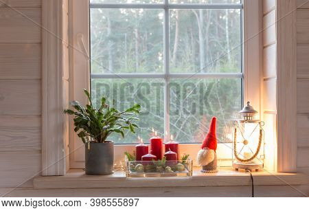 Christmas Lantern, Angel, Christmas Gnome, Christmas Cactus And Red Mug On The Window Of A Wooden Ho