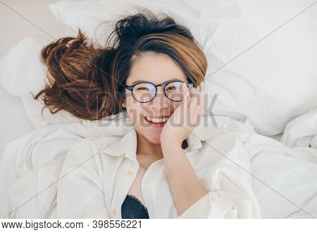Portrait Of Young Attractive Asian Woman Lying And Relaxing On Comfortable Bed And Looking To Camera