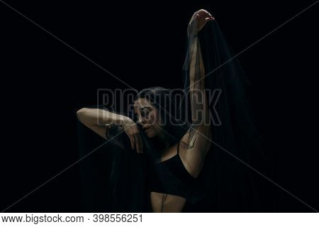 Scared. Graceful Classic Female Ballet Dancer Isolated On Black Studio Background. Woman In Minimali