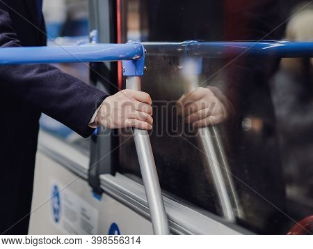 Selective Focus On A Passengers Male Hand Holding A Handrail In Public Transport. Concept Of Risk Of