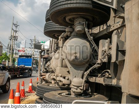 Close-up Of A View Of Under The Truck Carrying A Container Overturned On A Road Under A Bridge Over