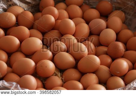 Pile Of Brown Organic Eggs At Farmers Market. Sale Of Domestic Chicken Eggs Close Up. Food Industry.