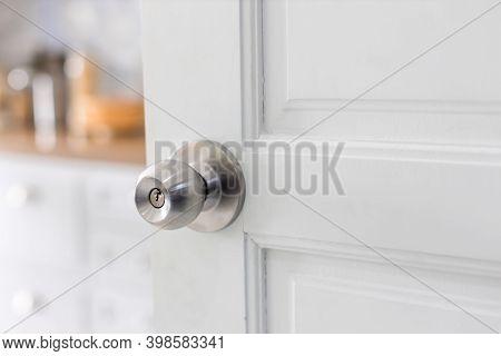 Door With Grill, Stainless Door Knob Or Handle On Wooden Door In Beautiful Lighting. A Handle On A D