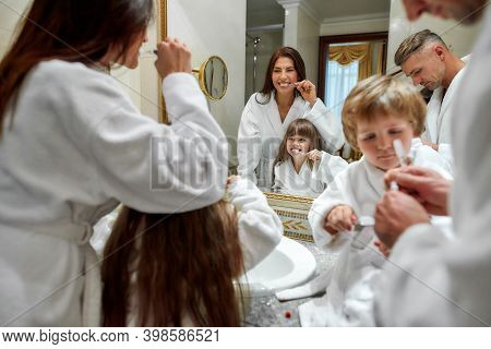 Caucasian Parents And Two Kids In White Bathrobes Having Morning Routine In Hotel Bathroom, Brushing
