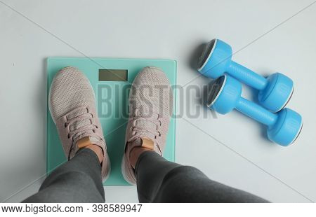 Losing Weight, Diet, Fitness Concept. Sport Woman Wearing Leggings And Sneakers Measures Her Weight