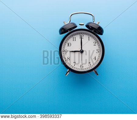 Black Retro Alarm Clock Showing Nine O'clock, Closeup Top View Clipping Path, Isolated On Blue Backg