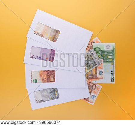 Stack Of Closed White Envelopes With Euro Bills Inside And Banknotes Beside Over Yellow Background.