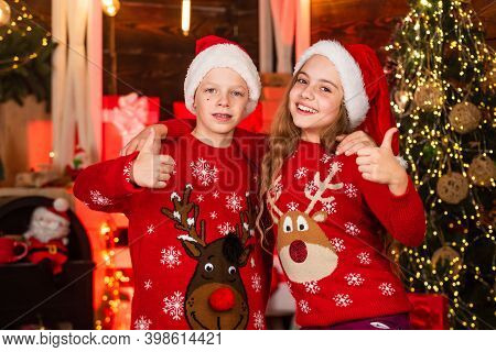 Sweater Outfit. Boy And Girl Santa Claus Hats. Kids Friends Meet Christmas Holiday. Joy And Noel. Fa