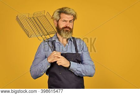 Tools For Roasting Meat. Man In Apron Hold Barbecue Grill. Chef Cooking Bbq Food. Summer Picnic. Hip