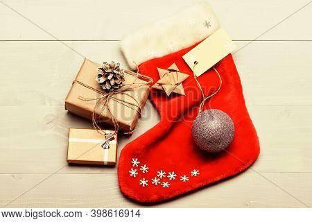 Santa Stocking With Christmas Gift Box. Christmas Decorative Sock Light Background Top View. Attribu