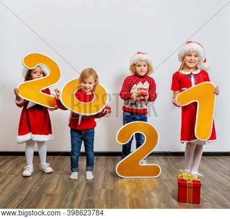 Four Funny Little Girls In Santa's Helper Costumes Stand With Big New Year Numbers On A White Backgr