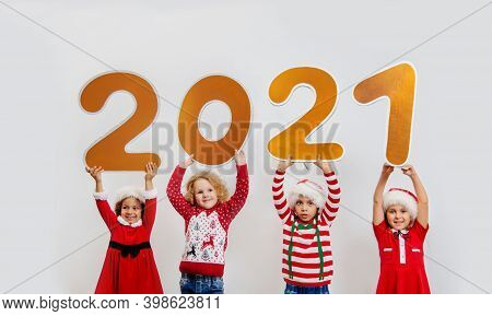 Four Funny Girls In Santa's Helper Costumes Stand With Big New Year's Numbers And Hold Them Above Th