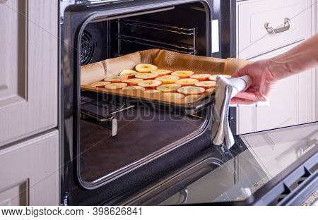 A Woman Housewife Puts A Baking Sheet Of Sliced Apples Into An Electric Oven To Dry. Dried Fruits, H
