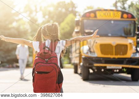 Mother Brings Her Daughter To School Near The School Bus. Back To School