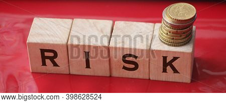 Risk Word Written On Wooden Cubes And Coins. Financial Risk Assessment, Risk Reward And Portfolio Ri