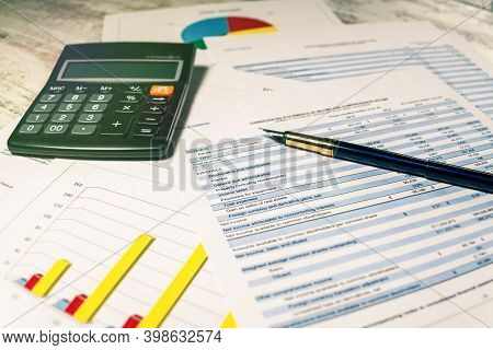 Calculator And Pen With Accounting Report And Financial Statement On Desk