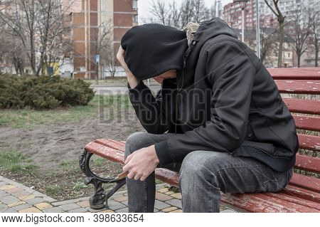 Addict Experiencing A Drug Addiction Crisis, Outdoors With A Syringe In His Hand. Lifestyle, Addicti