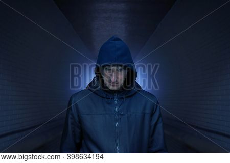 A Man In A Hood On The Street, In A Dark Alley. Addiction Concept. Tinted Photo