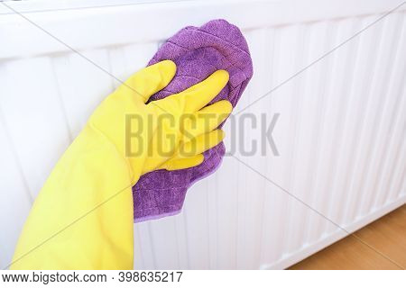 Employee Of Commercial Cleaning Company Wiping A Heater Radiator, Hand In Yellow Rubber Gloves Wipin