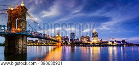 Nighttime panoramic view of John A. Roebling Suspension Bridge over the Ohio River and downtown Cincinnati skyline