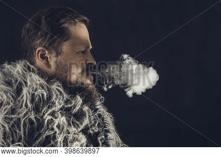 Solid Bearded Man Dressed In A Fur Mantle Exhaling Vapour