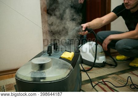 The Process Of Cleaning Carpets With A Steam Vacuum Cleaner. An Employee Of A Cleaning Company Prepa