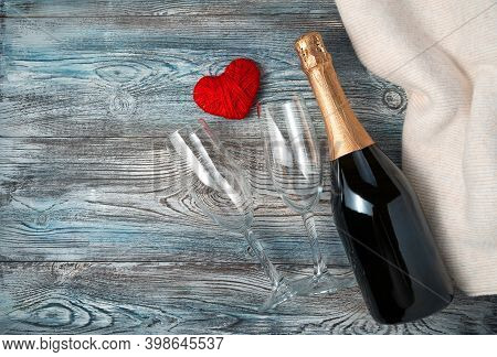 A Bottle Of Champagne, Two Glasses And A Heart On A Wooden Background With A Sweater.