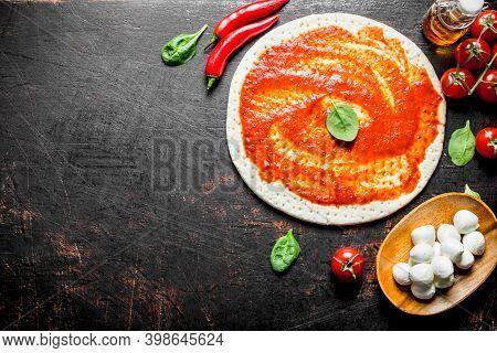 Preparation Pizza. Rolled Out Dough With Tomato Paste, Chili Pepper And Mozzarella. On Dark Rustic B