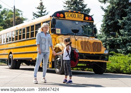 Mother Escorts The Schoolgirl With Ponytails And A Backpack To School.