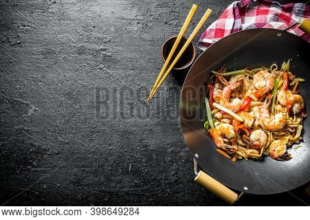 Delicious Chinese Wok Udon Noodles With Fresh Vegetables, Sauce And Shrimp. On Black Rustic Backgrou