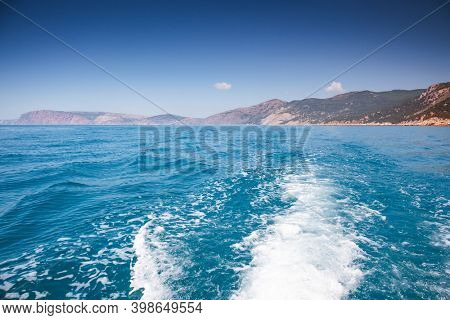 Powerful water stream after speed motorboat. Trail on water surface behind of fast moving boat. Fantastic view of the azure sea. Scenic image of summer holiday season. Discover the beauty of earth.