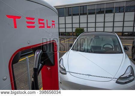 Dietikon, Switzerland - November 24, 2020: Tesla's Fast Charging Station And A Tesla Model 3 Electri