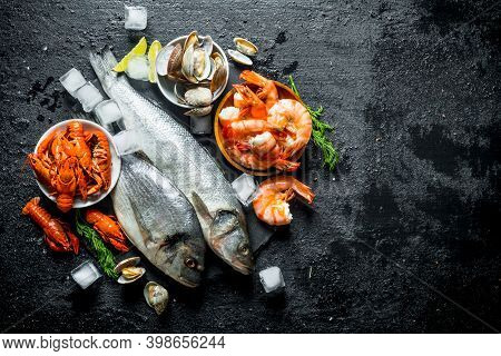 Raw Fish And Seafood On A Stone Board With Ice Cubes And Lime Slices. On Black Rustic Background