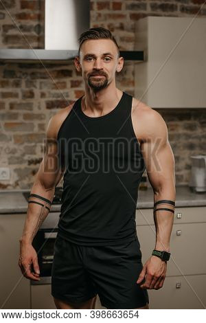 A Kind Muscular Man With A Beard Is Posing In His Apartment After A Workout. An Athletic Guy With Ta