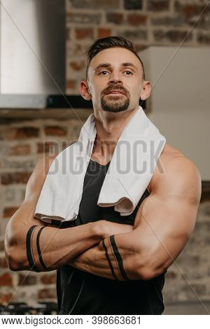 A Muscular Man With A White Towel On The Shoulders Is Posing With Folded Arms On His Chest In His Ap