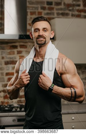 A Smiling Muscular Man With A Beard Is Holding The Ends Of The Towel Over His Neck In His Apartment.