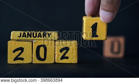 Wooden Block Calendar With A Focus On 2021 And January. There Is A Man's Hand Placing A Wooden Block