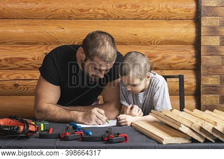 Dad And Son Are Drawing On Paper, Planning How To Build A Bird House, Tools And A Beam On The Table