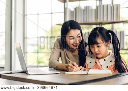 Mother And Asian Kid Little Girl Learning And Looking At Laptop Computer Making Homework Studying Kn