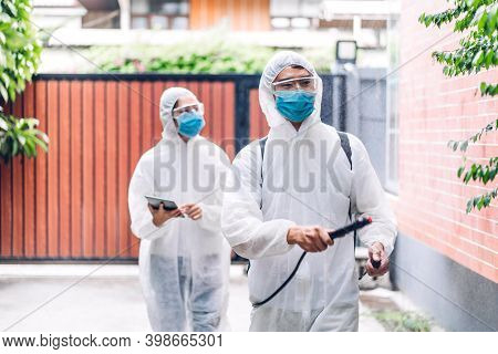 Professional Teams For Disinfection Worker In Protective Mask And White Suit Disinfectant Spray Clea